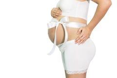 La mujer embarazada da sostener el vientre con el regalo blanco de la cinta en belio Fotos de archivo
