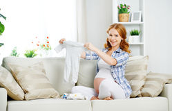 La mujer embarazada de la mujer embarazada prepara los artículos de la ropa para el newb Foto de archivo
