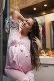 La mujer embarazada de los jóvenes aplica el pelo con brocha. fotografía de archivo