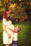 La mujer embarazada de los jóvenes camina con su hija Abrazo de la muchacha su Imágenes de archivo libres de regalías
