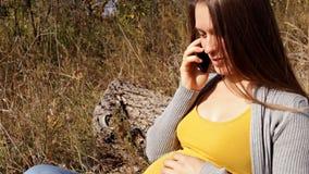 La mujer embarazada de los jóvenes habla por el teléfono almacen de video