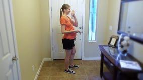 La mujer embarazada de los jóvenes rocía el espray de insecto en sí misma antes de ir al aire libre almacen de video