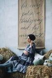 La mujer embarazada del caucásico con compone en vestido gris y se sienta en las balas del heno, retrato de la madre futura, feli imágenes de archivo libres de regalías