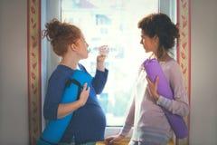 La mujer embarazada del pelo rojo hace una pausa la ventana con el instructor de la yoga Imagen de archivo libre de regalías