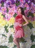 La mujer embarazada delante de las flores Fotografía de archivo libre de regalías