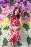 La mujer embarazada delante de las flores Imágenes de archivo libres de regalías