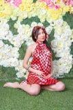 La mujer embarazada delante de las flores Foto de archivo