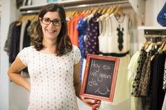 La mujer embarazada en ropa almacena la mirada de un poco de ropa Fotografía de archivo libre de regalías