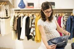 La mujer embarazada en ropa almacena la mirada de un poco de ropa Fotografía de archivo