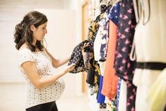 La mujer embarazada en ropa almacena la mirada de un poco de ropa Foto de archivo libre de regalías