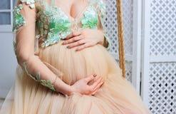 La mujer embarazada en vestido lleva a cabo las manos en el vientre en un fondo blanco Concepto del embarazo, de la maternidad, d Foto de archivo