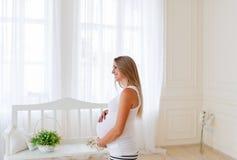 La mujer embarazada está en el cuarto ligero Imagen de archivo libre de regalías