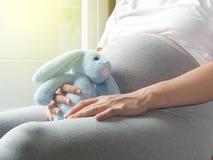 La mujer embarazada está jugando la muñeca del conejo en su mano Fotografía de archivo
