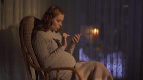 La mujer embarazada está mandando un SMS en el teléfono celular La señora muestra su vientre en la pantalla a su interlocutor almacen de metraje de vídeo