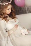 La mujer embarazada feliz admira los zapatos de los niños Fotos de archivo libres de regalías