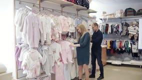 La mujer embarazada feliz con su marido en una tienda de ropa del ` s de los niños elige la ropa para el bebé almacen de video