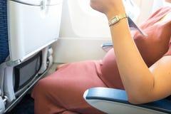La mujer embarazada feliz está viajando al destino por sittin plano Foto de archivo