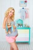 La mujer embarazada feliz sostiene un juguete de la felpa Fotos de archivo