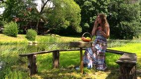 La mujer embarazada feliz tiene comida campestre en banco cerca del agua de río almacen de metraje de vídeo
