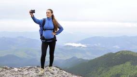 La mujer embarazada hace el selfie en la montaña almacen de metraje de vídeo