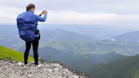 La mujer embarazada hace la foto en la montaña almacen de video