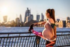 La mujer embarazada la hace que estira en la ciudad imágenes de archivo libres de regalías