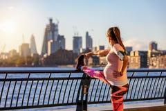 La mujer embarazada la hace que estira en Londres imagenes de archivo