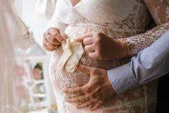 La mujer embarazada hermosa joven y su marido con las manos en su vientre guarda los calcetines blancos del bebé en su vientre Foto de archivo