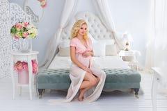La mujer embarazada joven se sienta en una cama Imagenes de archivo