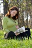 La mujer embarazada lee el libro Foto de archivo
