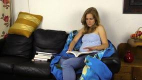 La mujer embarazada leyó el libro en el sofá y acaricia su vientre del estómago metrajes