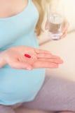 La mujer embarazada linda está bebiendo las vitaminas Fotos de archivo