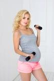 La mujer embarazada lleva a cabo pesas de gimnasia Foto de archivo