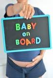 La mujer embarazada lleva a cabo un texto coloreado del bebé a bordo en la pizarra sobre su vientre Foto de archivo