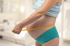 La mujer embarazada mide su vientre. Imagenes de archivo