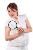 La mujer embarazada mira a través de la lupa Imágenes de archivo libres de regalías
