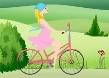 La mujer embarazada monta una bici a través del campo Fotos de archivo libres de regalías