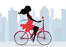 La mujer embarazada monta una bicicleta en el fondo de la ciudad Foto de archivo libre de regalías