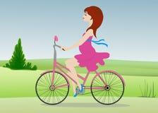La mujer embarazada monta una bicicleta a través del campo Imagen de archivo libre de regalías