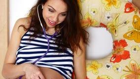 La mujer embarazada que es examina con el estetoscopio