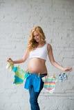 La mujer embarazada que presenta con el ` s de los niños viste en un fondo de la pared de ladrillo Imagenes de archivo