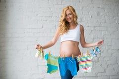 La mujer embarazada que presenta con el ` s de los niños viste en un fondo de la pared de ladrillo Fotografía de archivo