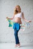 La mujer embarazada que presenta con el ` s de los niños viste en un fondo de la pared de ladrillo Fotos de archivo libres de regalías
