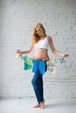 La mujer embarazada que presenta con el ` s de los niños viste en un fondo de la pared de ladrillo Foto de archivo libre de regalías