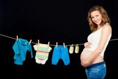 La mujer embarazada que se coloca con el ` s de los niños viste en un fondo negro Imagen de archivo