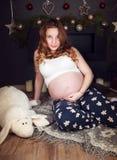 La mujer embarazada que se sienta en el fondo de la chimenea adornada con la Navidad juega Fotos de archivo