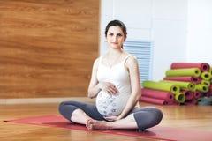 La mujer embarazada que se sienta en la estera de la yoga, guarda las manos del vientre Imágenes de archivo libres de regalías