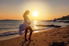 La mujer embarazada se coloca en la playa y se sostiene el vientre durante tiempo de la puesta del sol foto de archivo libre de regalías
