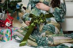 La mujer embarazada se está sentando cerca del árbol de navidad en casa imagenes de archivo