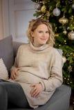 La mujer embarazada se está sentando en un sofá en la Navidad imagenes de archivo